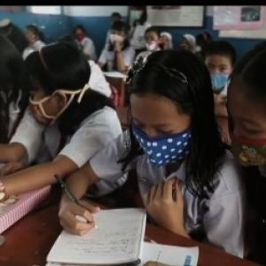 A Singapour, des enfants se protegent de la fumee toxique qui emane de l incendie des forets