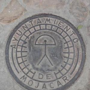 AW 020010 Mojacar : la representation de l Indalo ( = messager des Dieux ) se rencontre partout ( ici, sur un couvercle d egout )