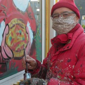 Jean-Marie Lesage terminant au pinceau le noir de la décoration sur une vitrine. Photo de Sandra Deruère, photographe pour le site de la ville d'Arcueil (Paris)