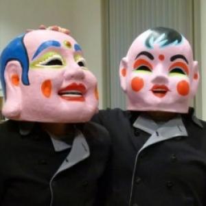 """Deux masques portes devant des photos en milieu occidental (c) """"DH"""""""