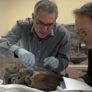 """Prelevement d'un cheveu d'une momie amerindienne, sous le regard attentif de Serge Lemaitre (c) """"Panoramique Terre Productions"""""""