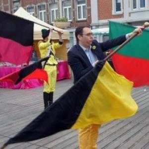 """Le Bourgmestre de Namur, Maxime Prevot, jouant du drapeau au sein des """"Alfers"""" (c) """"Folknam"""""""