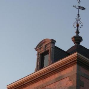 Une courte aile en retour surmontee d'une girouette datant de 1869