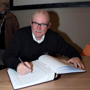 M. Distree, President, signant le Livre d'Or ( Photo de G. Blanchy )