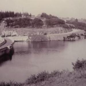 Ca y est, le lac est plein. Les eaux sont arrivees au panneau 496 accroche au mur protegeant le mecanisme de la vanne de la prise d'eau situee a la cote 466, 30 m plus bas. Dans le fond, les grosses limousines appartiennent a la direction de la Sofina