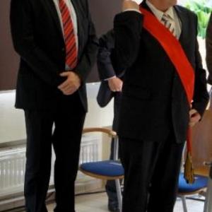 22. Le Commissaire d'arrondissement, Albert Stassen, ajuste son echarpe