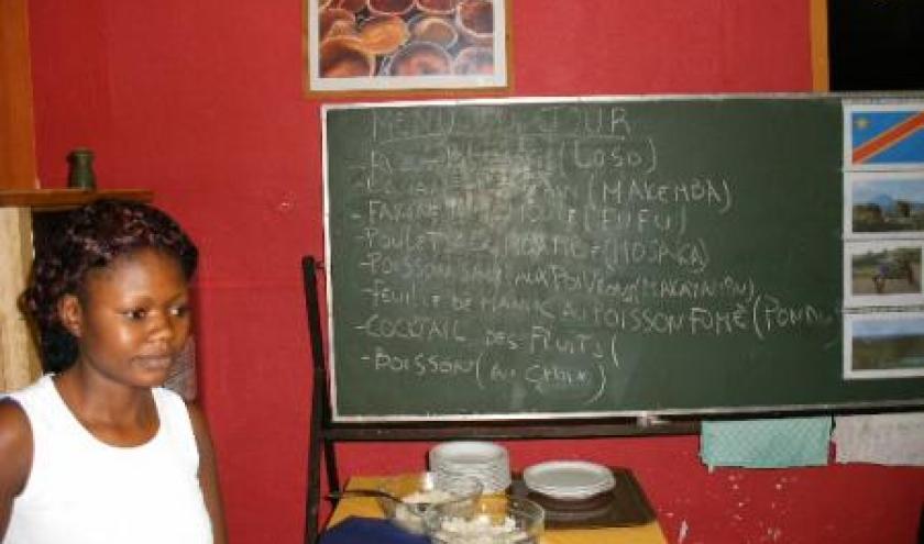 Evelyne devant le menu: loso, makemba; fufu, mosaka, makayambu, pondu